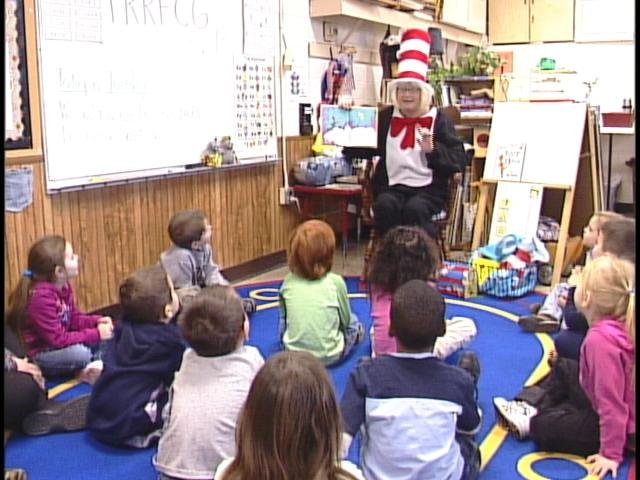 Troyce Vich, dressed as the Cat in the Hat, reads to students.
