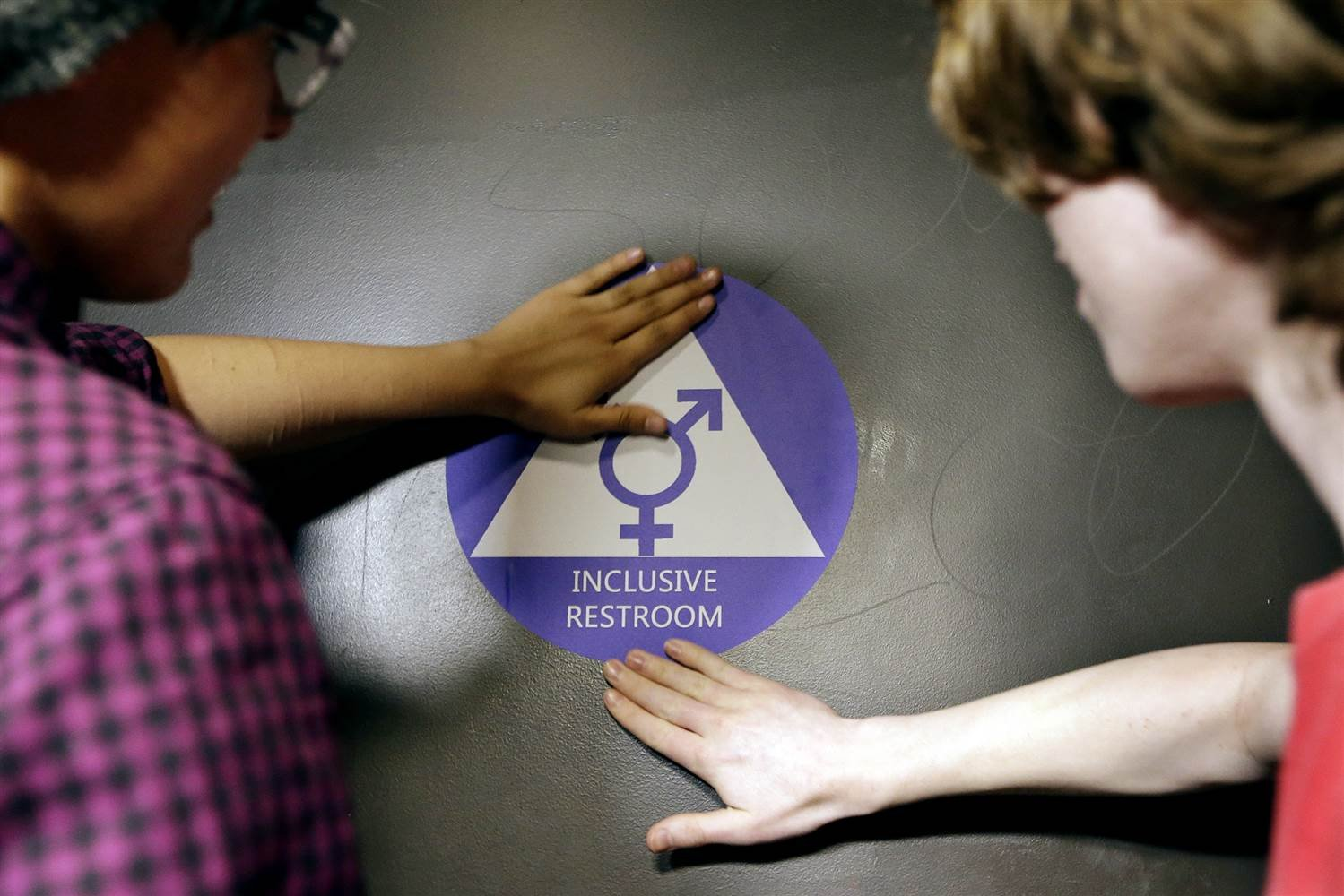 "Destin Cramer and Noah Rice place a new sticker on the door at the ceremonial opening of a gender neutral bathroom at Nathan Hale high school, May 17 in Seattle. Elaine Thompson / AP Publication is intended ""to clarify that discrimination on the basis of"