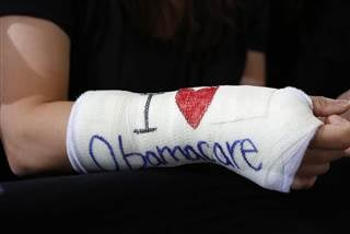 """Cathey Park of Cambridge, Massachusetts wears a cast for her broken wrist with """"I Love Obamacare"""" written upon it KEVIN LAMARQUE / Reuters file"""