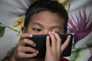 A child looks at a mobile phone Donal Husni / NurPhoto via Getty Images