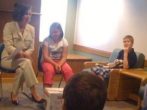 First Lady of Iowa Mari Culver talks with children at Hillcrest Family Services about the importance of reading. Mrs. Culver's daughter sits to her left.