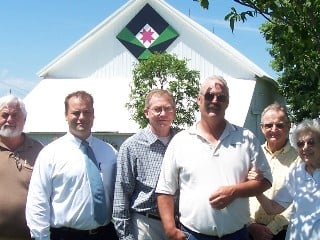 The Washington County supervisors posed with John and Dorothy Helscher outside their quilt-displaying barn.