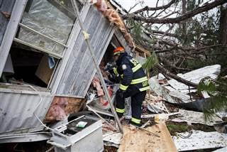 A rescue worker enters a hole in the back of a mobile home, Jan. 23 in Big Pine Estates that was damaged by a tornado, in Albany, Georgia. Branden Camp / AP