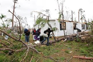 Lasheree Richardson, Charlee Daly, Rochelle Vaughn and Deanna Furlow remove belongings from their home after a tornado struck the residential area in Albany, Georgia, on Jan. 23. Tami Chappell / Reuters