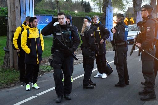 (AP Photo/Martin Meissner). Dortmund's Marcel Schmelzer talks to police officers outside the team bus after it was damaged in an explosion before the Champions League quarterfinal soccer match between Borussia Dortmund and AS Monaco in Dortmund, wester...