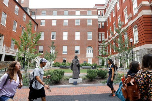 (AP Photo/Jacquelyn Martin, File). FILE - In this Sept. 1, 2016, file photo, students walk past a Jesuit statue in front of Freedom Hall, center, formerly named Mulledy Hall, on the Georgetown University campus in Washington, D.C.