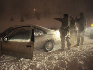 Sfc. Shaun Jenson and Pfc. Aaron Last marked a disabled car and transported its driver to a safe location during the storm. Photo Courtesy of the Iowa National Guard