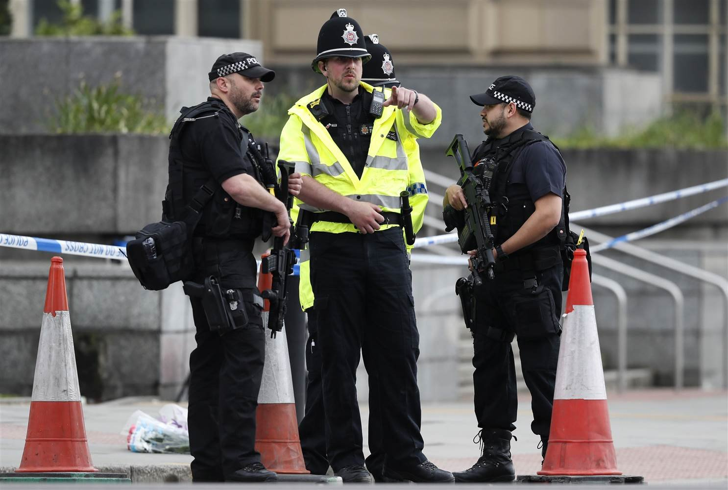 Armed police officers patrol a police cordon near the Manchester Arena in Manchester on May 24. Kirsty Wigglesworth / AP