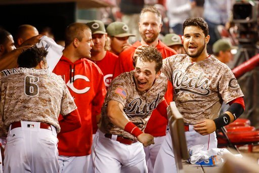 (AP Photo/John Minchillo). Cincinnati Reds' Scooter Gennett, center, celebrates in the dugout after hitting a two-run home run and his fourth overall in the eighth inning of a baseball game against the St. Louis Cardinals, Tuesday, June 6, 2017.