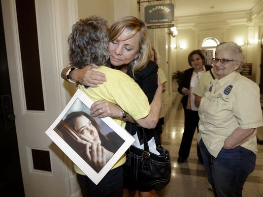 In this Sept. 9, 2015, file photo, Debbie Ziegler holds a photo of her late daughter, Brittany Maynard, as she receives congratulations from Ellen Pontac, left, after a right-to die measure was approved by the state Assembly in Sacramento, Calif. (AP)