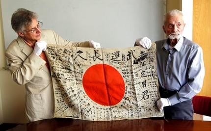 In this Monday, Aug. 7, 2017 photo, WWII veteran Marvin Strombo, right, and Obon Society executives director Rex Zika hold up a Japanese flag with names written on it in Portland, Ore. Strombo recovered the flag from a dead Japanese soldier in the Pacific