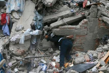 A construction worker searches a building that collapsed after an earthquake, in the Roma neighborhood of Mexico City, Tuesday, Sept. 19, 2017.  AP Photo/Eduardo Verdugo