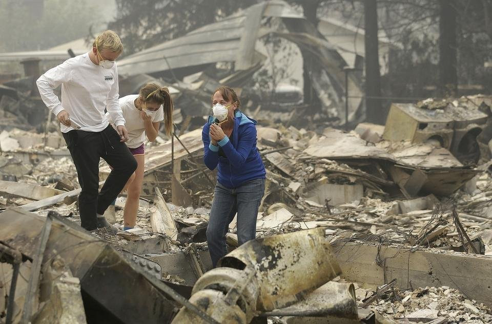 Mary Caughey, center in blue, reacts with her son Harrison, left, after finding her wedding ring in debris at her home destroyed by fires in Kenwood, Calif., Tuesday, Oct. 10, 2017. (AP Photo/Jeff Chiu)