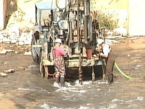 A drill rig bores samples of rock at the Lake Delhi dam site