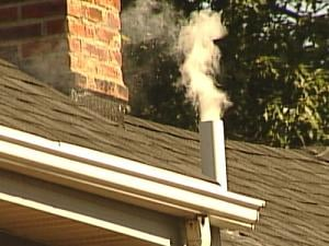 Smoke pours out of a pipe atop the roof of a Dubuque home