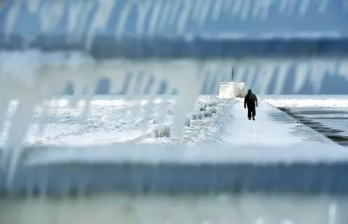 (Don Campbell/The Herald-Palladium via AP). A man walks along the ice-covered south pier Thursday. Feb. 8, 2018, in St. Joseph, Mich.