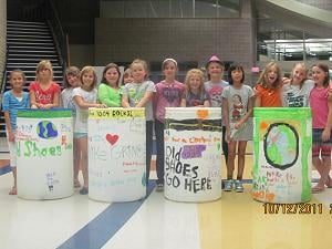 Girl Scouts in troop 7004 stand in front of their then-empty shoe recycling bins in October