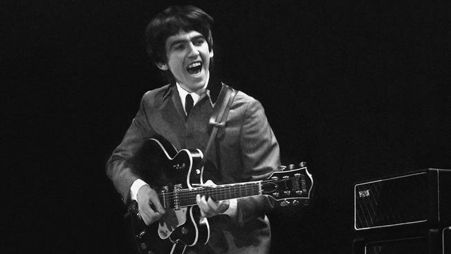 This February 11, 1964 photo provided by Christie's auction house, from a collection of photos of The Beatles shot by photographer Mike Mitchell at the Washington Coliseum in Washington, D.C., shows George Harrison during the group's first US concert, two
