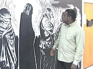 "Will Pearsall stands next to his mural, a recreation of ""Christ of the Breadlines,"" by Fritz Eichenberg"