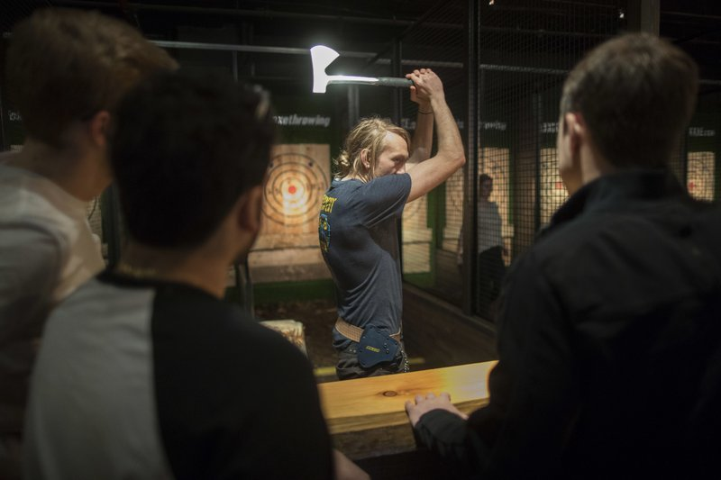 "In this March 3, 2018, photo, an ""axpert,"" center, gives contestants instruction on hatchet throwing techniques and the rules of the game at the Kick Axe Throwing venue in the Brooklyn borough of New York. (AP Photo/Mary Altaffer)"