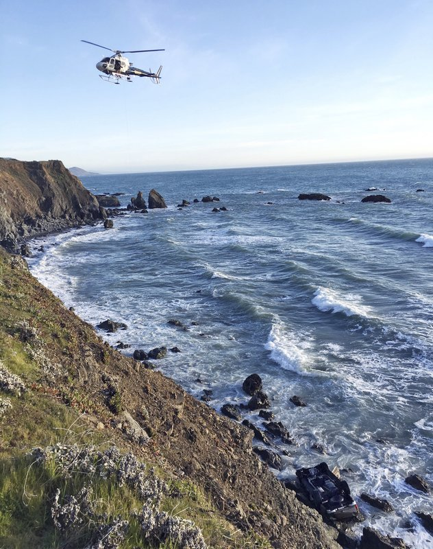 (California Highway Patrol via AP). This photo provided by the California Highway Patrol shows a helicopter hovering over steep coastal cliffs Tuesday, March 27, 2018, near Mendocino, Calif., where a vehicle, visible at lower right, plunged about 100 f...