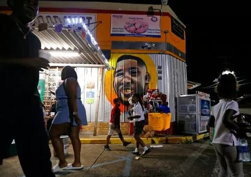 (AP Photo/Gerald Herbert, File). FILE - In this May 2, 2017, file photo, people congregate in front of a mural of Alton Sterling outside the Triple S Food Mart, where Sterling was killed in 2016, in Baton Rouge, La.
