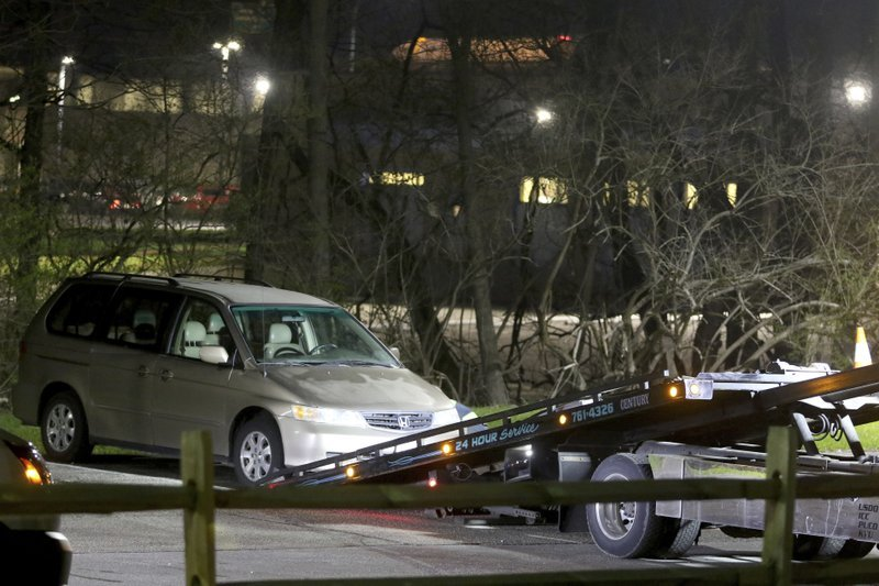 In this Tuesday night, April 10, 2018 photo, a minivan is removed from the parking lot near the Seven Hills School campus in Cincinnati. (Cara Owsley/The Cincinnati Enquirer via AP)