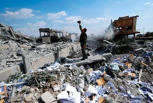 (AP Photo/Hassan Ammar, File). FILE - In this Saturday, April 14, 2018 file photo, a Syrian soldier films the damage of the Syrian Scientific Research Center which was attacked by U.S., British and French military strikes...