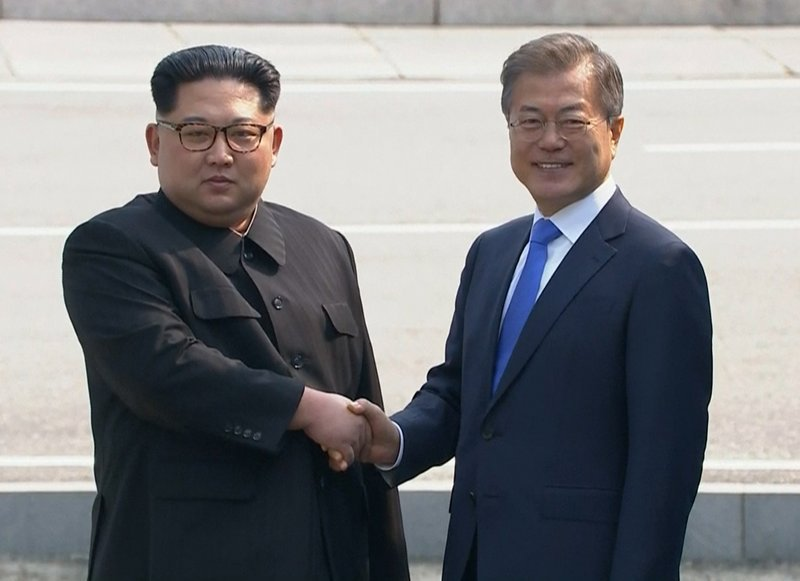 In this image taken from video provided by Korea Broadcasting System (KBS) Friday, April 27, 2018, North Korean leader Kim Jong Un, left, shakes hands with South Korean President Moon Jae-in as Kim crossed the border into South Korea for their historic fa