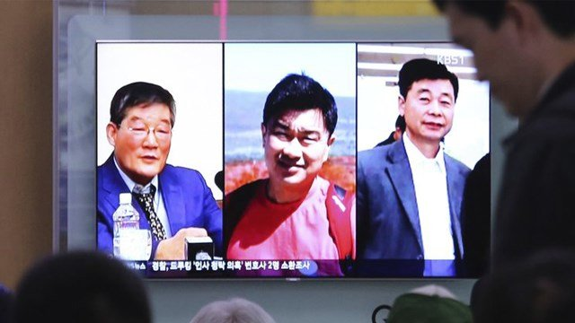 In this May 3, 2018 photo, people watch a TV news report on screen, showing portraits of three Americans, Kim Dong Chul, left, Tony Kim and Kim Hak Song, right, detained in the North Korea, at the Seoul Railway Station (AP Photo/Ahn Young-joon)