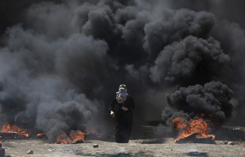 A Palestinian woman walks through black smoke from burning tires during a protest on the Gaza Strip's border with Israel, Monday, May 14, 2018. Thousands of Palestinians are protesting near Gaza's border with Israel, as Israel prepared for the festive ina