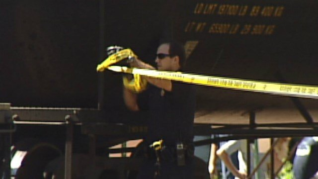 A Waterloo P.D. officer tapes off the scene after a woman was rolled over by a train while trying to cross through it in September 2011.
