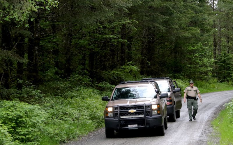 (Alan Berner/The Seattle Times via AP) Washington State Fish and Wildlife Police leave the scene on a remote King County road near the site of a fatal cougar attack Saturday May 19, 2018 in East King County, Wash. One man was killed and another seriously