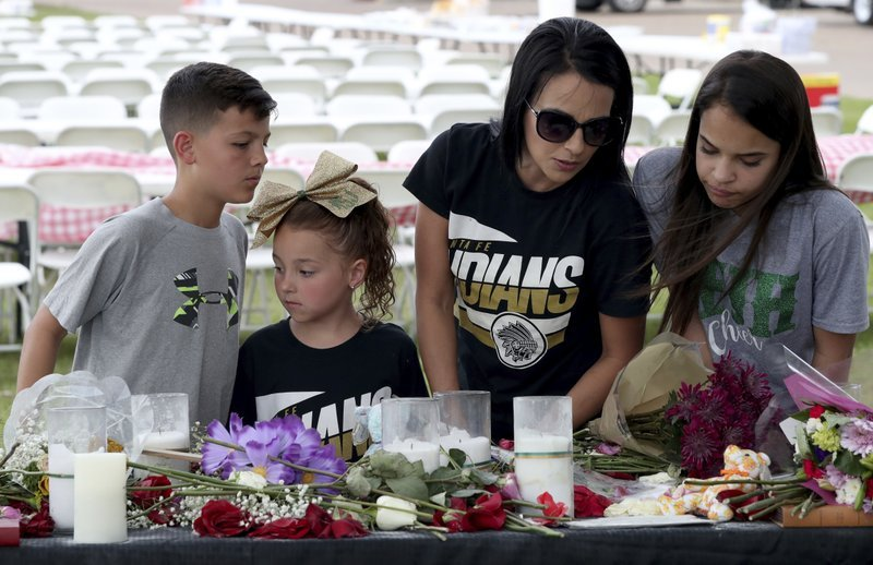 (Jennifer Reynolds/The Galveston County Daily News via AP). April Salinas, second from right, her daughters Meah, 13, and Macee, 6, and Jeramiah Kelley read notes left at memorial behind Texas First Bank, Saturday, May 19, 2018 in Santa Fe, Texas. A gu...