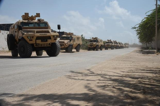 A convoy of armored troop carrying vehicles provided by the U.S. Department of Defense and Department