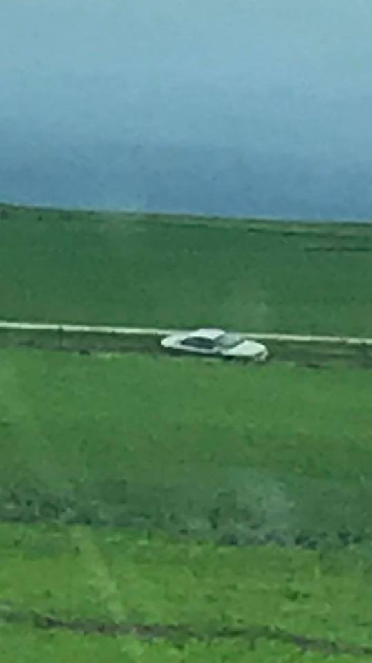 Photo of one car swept off the road by flooding. This was posted to Facebook by Kate Taylor.
