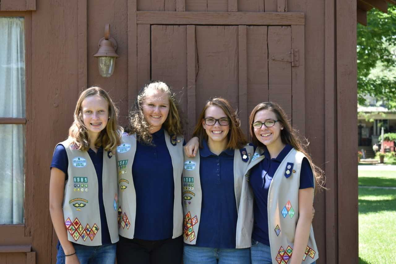 Standing in front of the replica cabin: Elise Wehr, Myah Brinker, Sydney Herzmann, and Audrienne Kennedy