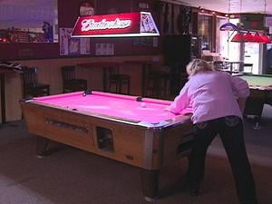 Cheryl Kramer plays pool at the table her husband got to mark her five years as a breast cancer survivor.