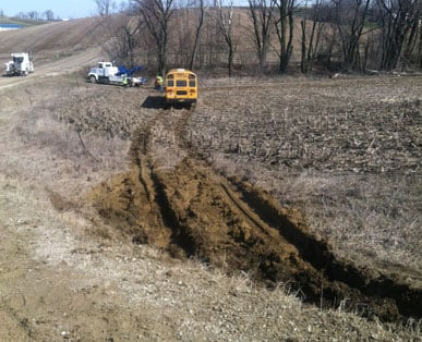 The bus came to rest in a field on its side before a towing company righted it.