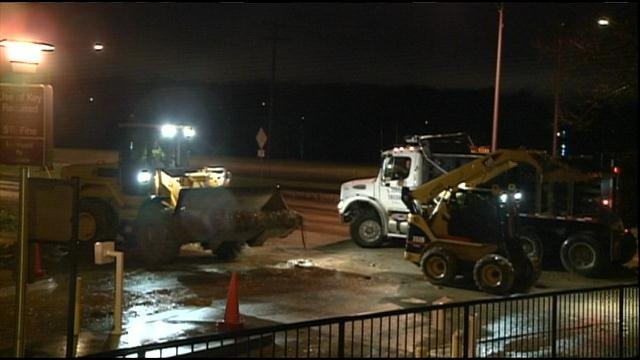 Crews clear away mud from the Mayflower parking lot.