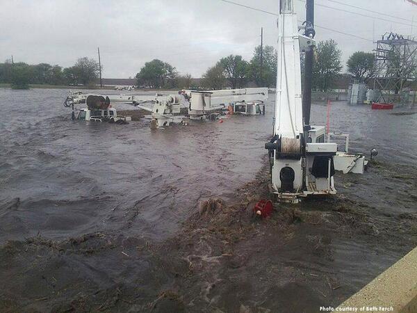 Utility trucks in flood waters near Beaman