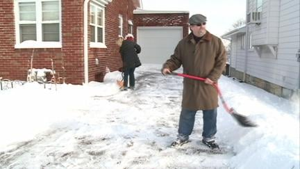 Paul Freisinger helps a neighbor shovel their driveway Sunday morning in Dubuque.