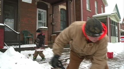 Alex Mihalakis and his 6 year-old-son Jace shoveling a sidewalk Sunday in Dubuque.