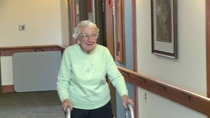 A resident of Stonehill's Center for Memory Care walks to her room after lunch
