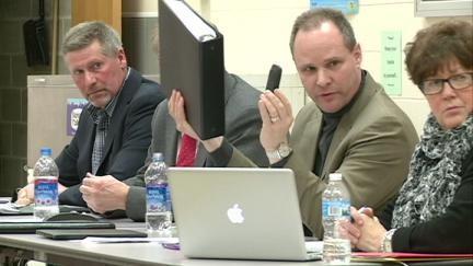 Lake Delhi board president Steve Leonard holds up 400-page final bid package, approved Monday night