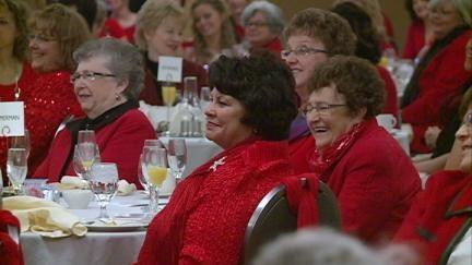 Women attending the Mercy Red Dress breakfast Friday in Dubuque enjoy keynote speaker Jeanne Robertson