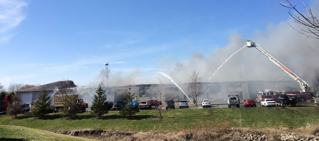 Firefighters work to extinguish a blaze at an industrial building on Heinz Road in Iowa City on Tuesday afternoon. (David Scrivner / Iowa City Press-Citizen)