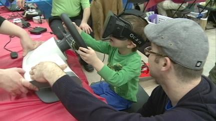 A little boy tries his hand at remotely driving a model vehicle Saturday at the Mini Maker Faire at the Cedar Rapids Science Center