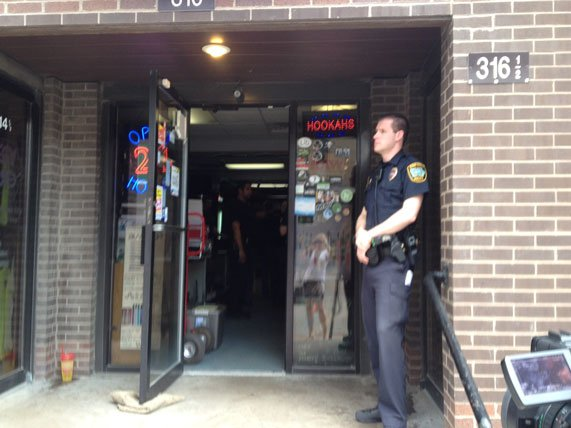 A police officer guards the door of Zombies in Iowa City during a synthetic drug raid May 7, 2014. The raid was part of a nationwide raid on similar shops.