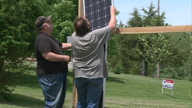 Steve Niedert (left) and his son John Niedert remove solar panels from John's front yard Thursday